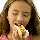 Close-up of a girl eating a hot dog