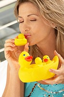 Close-up of a mid adult woman kissing a rubber duck