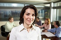 Young businesswoman in meeting room with colleagues, smiling, portrait