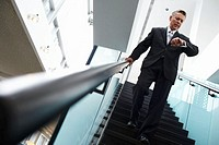 Businessman on stairs looking at watch, low angle view