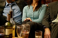 Woman sitting between two male colleagues in bar, mid section