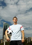 Young man standing holding football, portrait, low angle
