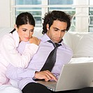 Close-up of a businessman and a businesswoman sitting on the bed using a laptop