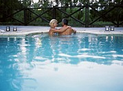 Couple in swimming pool, woman holding arms around man, smiling