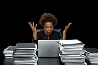 Businesswoman at desk by laptop and paperwork, hands raised