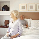 Senior couple in bedroom, woman sitting on end of bed holding cup