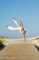 Young man balancing on hand  performing capoeira on beach path