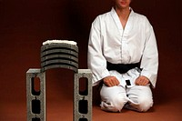 Blackbelt Kneeling Next To Stack of Concrete