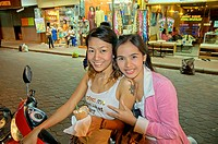 Thailand, Pattaya, 2 smiling girls on motorbike on Walking Street