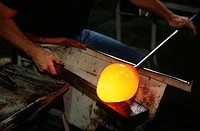 Man shaping and smoothing a parison, an intermediate shape of a glass object, at Blenko Glass, Milton, WV.