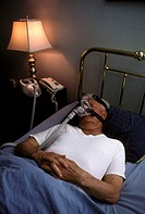 Male patient using a continuous positive airway pressure (CPAP) device, a respiratory ventilation apparatus developed to treat sleep apnea patients, b...