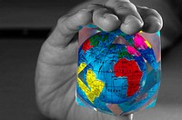 Black and white picture of hand holding a colourful globe