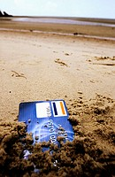 Credit card being covered with sand