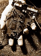 Hand holding a destroyed circuit board