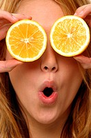 A woman with her mouth rounded using two slices of orange to cover her eyes