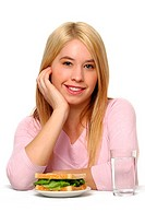 A blonde hair girl sitting at a table posing with a plate of sandwich and a glass of water