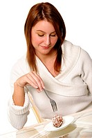 A woman looking down while holding a fork near to a plate of chocolate ball cake