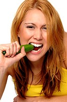 A woman in yellow spaghetti top biting a cucumber