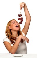 A woman holding up red grapes trying to eat it