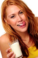 A woman licking her lips while holding a glass of milk
