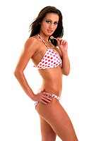 A woman in polka dots bikini eating lollipop