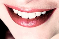 An up-close picture of a woman's red lips and white teeth