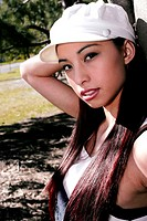 A young asian girl with white cap leaning against a tree