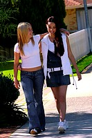 Two girlfriends hugging each other while walking back home