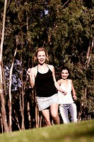 A girl in mini skirt running while her friend chasing her from behind