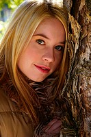 An up-close picture of a blonde hair girl posing beside a tree