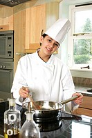 A boy disguising as a chef cooking in the kitchen