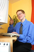 A boy in business suit working on a computer