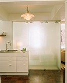Kitchen with a frosted glass sliding door hiding a small bedroom