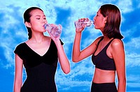 Two women drinking bottled water