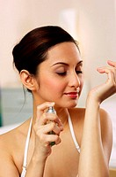 Woman spraying some perfume on her hand