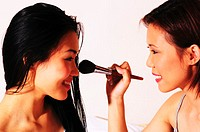 Woman helping her friend to apply some loose powder on her face