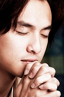 Man closing his eyes while praying