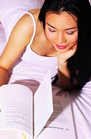 Woman reading book on the bed