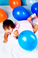 Baby girl playing with balloons