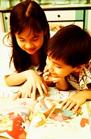Boy and girl sharing a story book