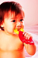 Baby girl biting on a teether