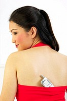 Woman keeping her mobile phone in her bare-back top (thumbnail)