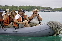 Eco-tourists-photographing-wildlife-from-small-boat,-near-Puerto-Villamil,-Isabela-Island,-Galapagos,-Ecuador