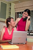 Women talking on the phone and using laptop