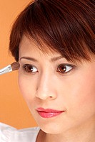 Woman applying eye shadow.