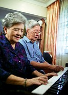Old couple playing piano