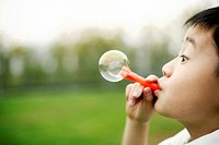 Boy blowing out soap bubble