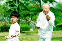 Boy practicing tai chi with his grandfather