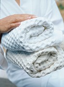 Woman holding rolled up towels