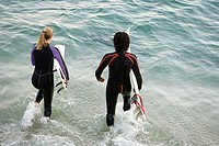 Surfers going into the sea